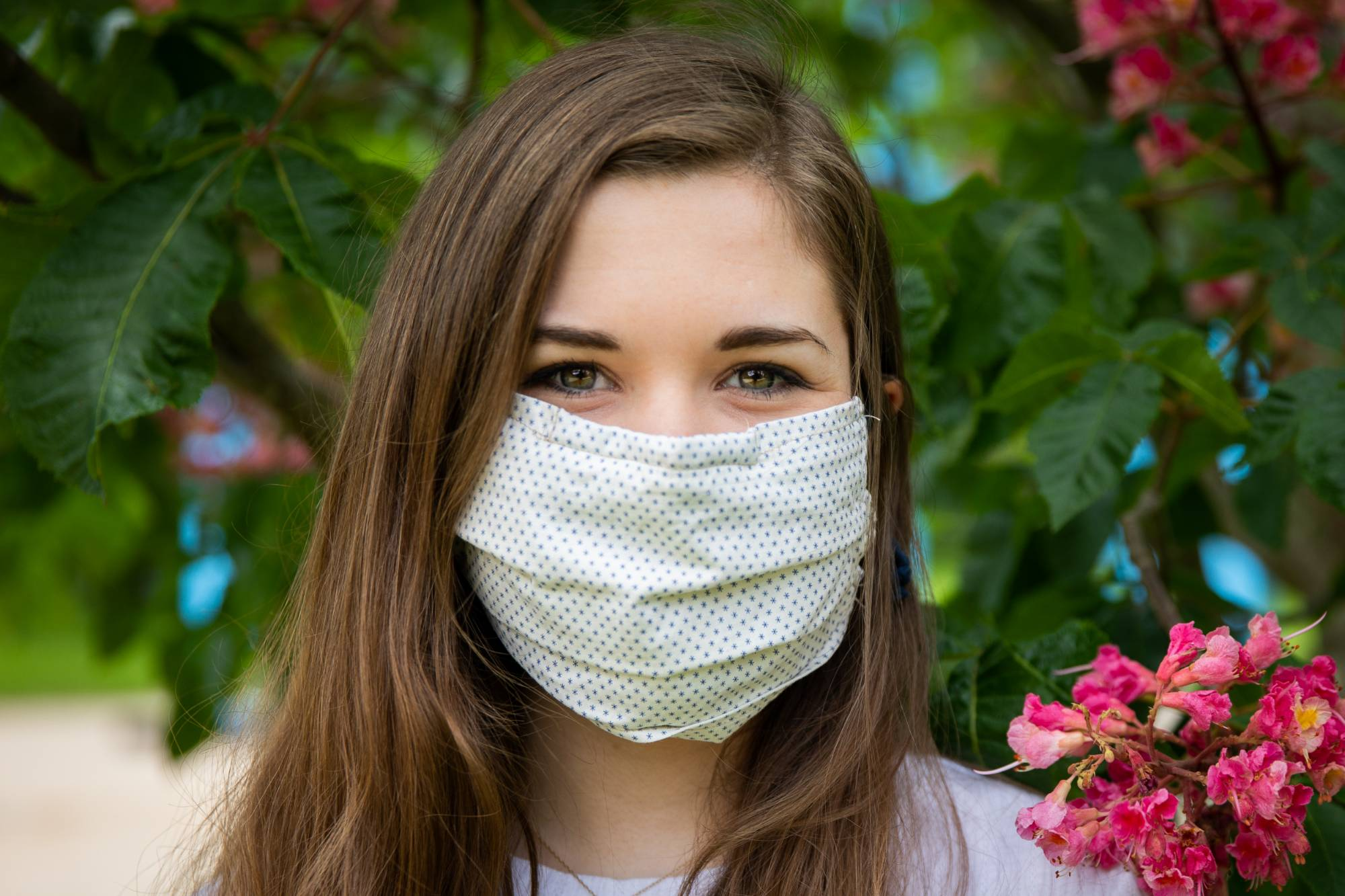 A current student stands near a plant wearing a face covering.